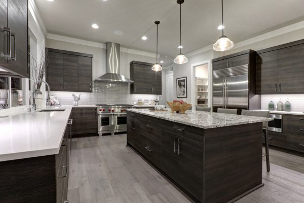 Modern gray kitchen features dark gray flat front cabinets paired with white quartz countertops and a glossy gray linear tile backsplash. Northwest, USA