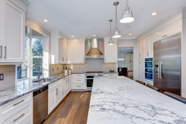 Luxury home interior boasts amazing white kitchen with custom white shaker cabinets, endless marble topped kitchen island and stainless steel appliances over wide planked hardwood floor.