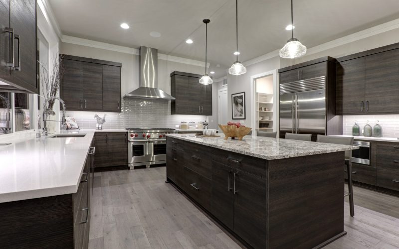 Modern gray kitchen features dark gray flat front cabinets paired with white quartz countertops and a glossy gray linear tile backsplash. Northwest, USA.